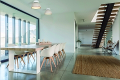 Domestic open space with dining table and wooden stairs